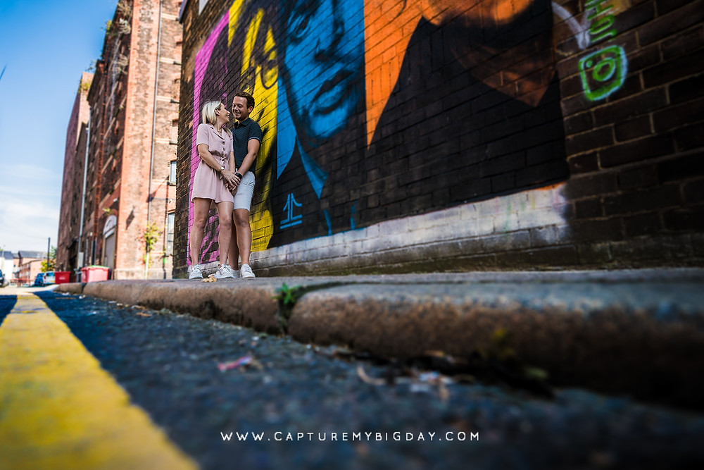 couple next to art painted on the wall in Liverpool