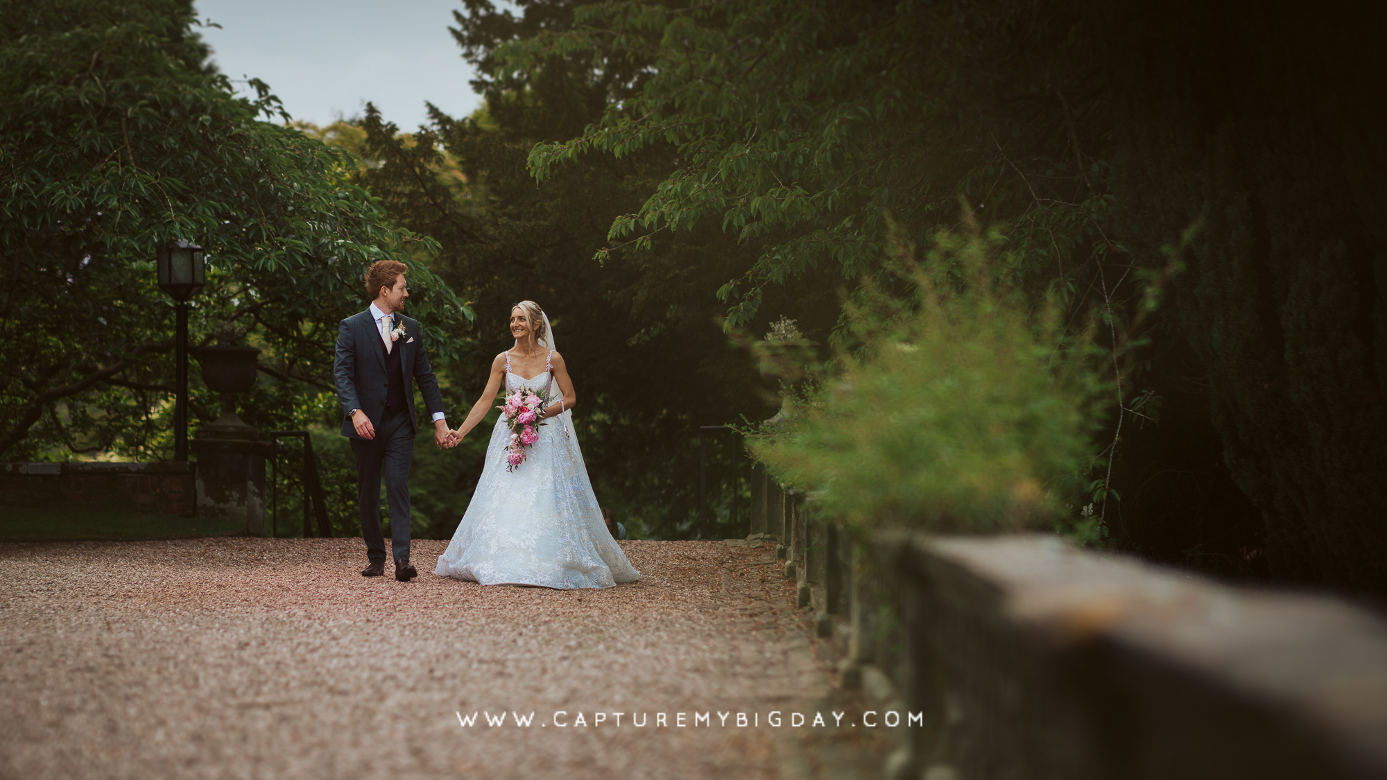 bride and groom walking grounds of capesthorne hall