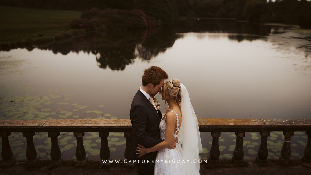 Bride and groom next to the lake at Capesthorne Hall