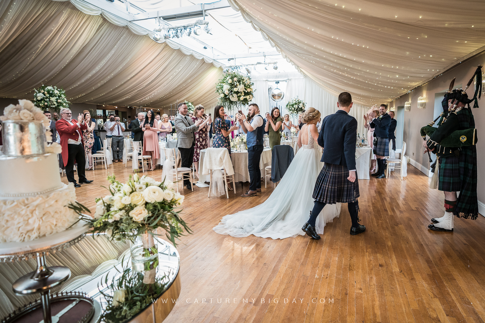 bride and groom walking in to wedding breakfast room with bagpiper