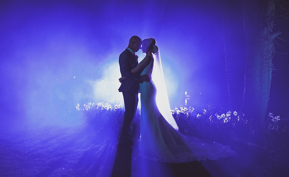 Bride and groom at night with blue light behind them