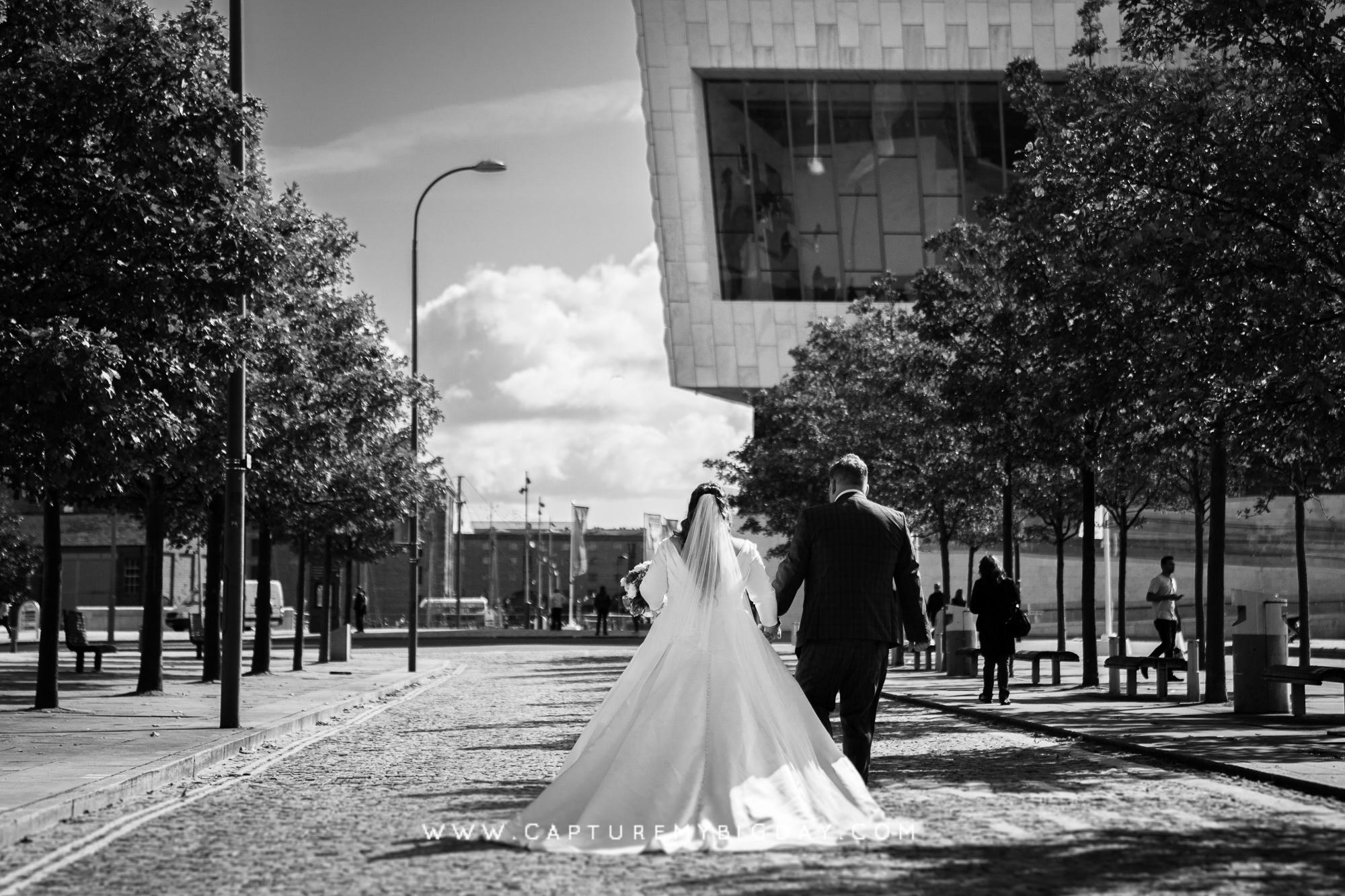 bride and groom walking in liverpool