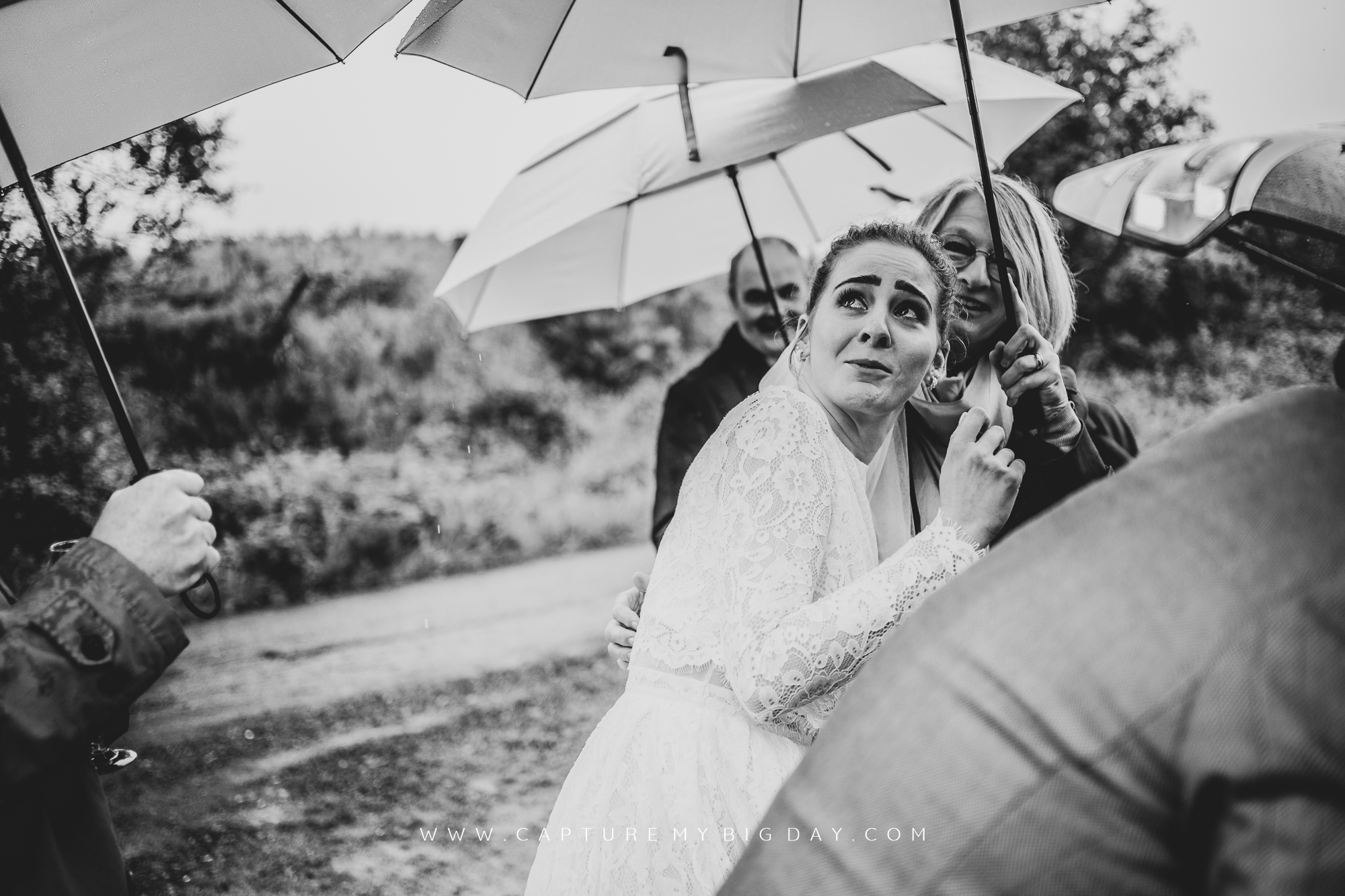 bride trying not to get wet under umbrella