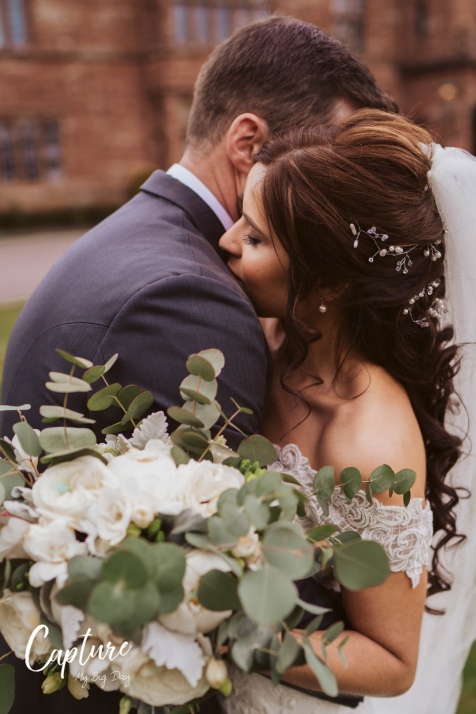 Bride and groom hugging outside Wrenbury Hall