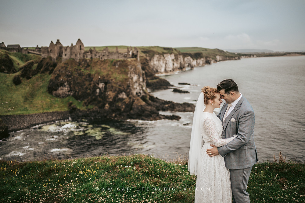 Bride and Groom on Cliff edge with castle in the background