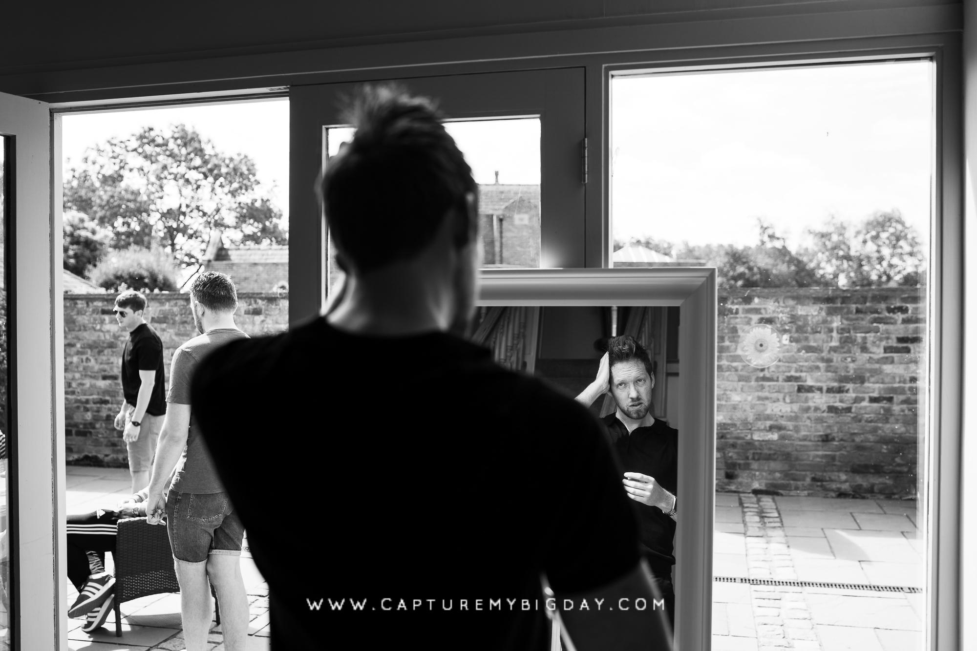 groom styling his hair in mirror