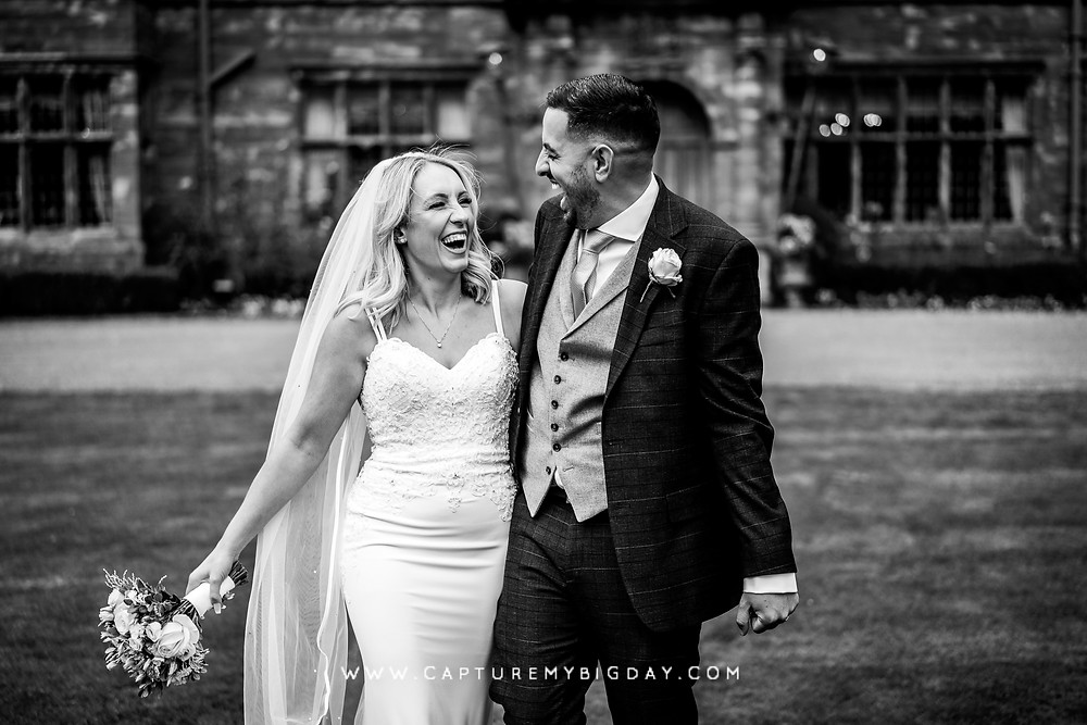 Bride and groom laughing while walking on the lawn of Wrenbury Hall