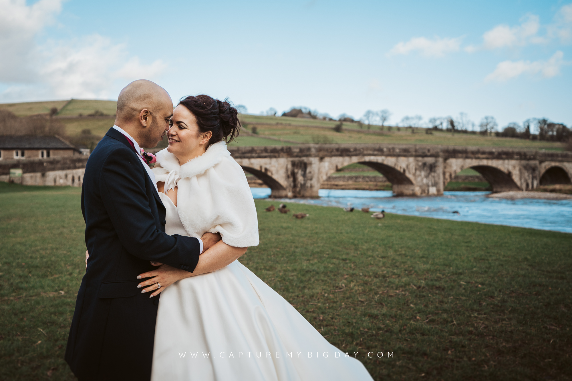 bride and groom by river with ducks