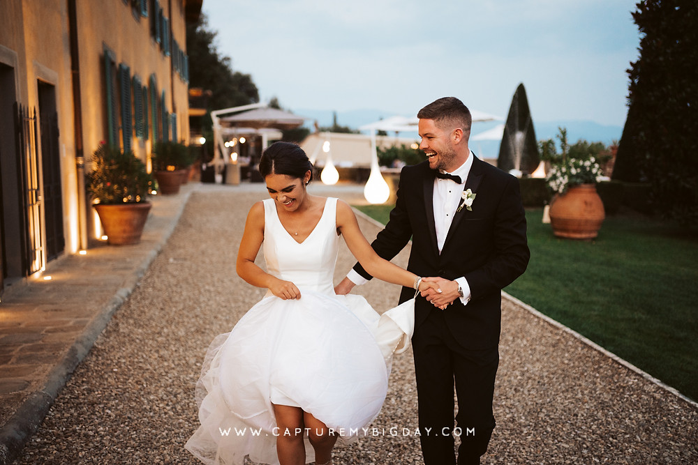 Bride and groom laughing and walking together in the evening in Italy