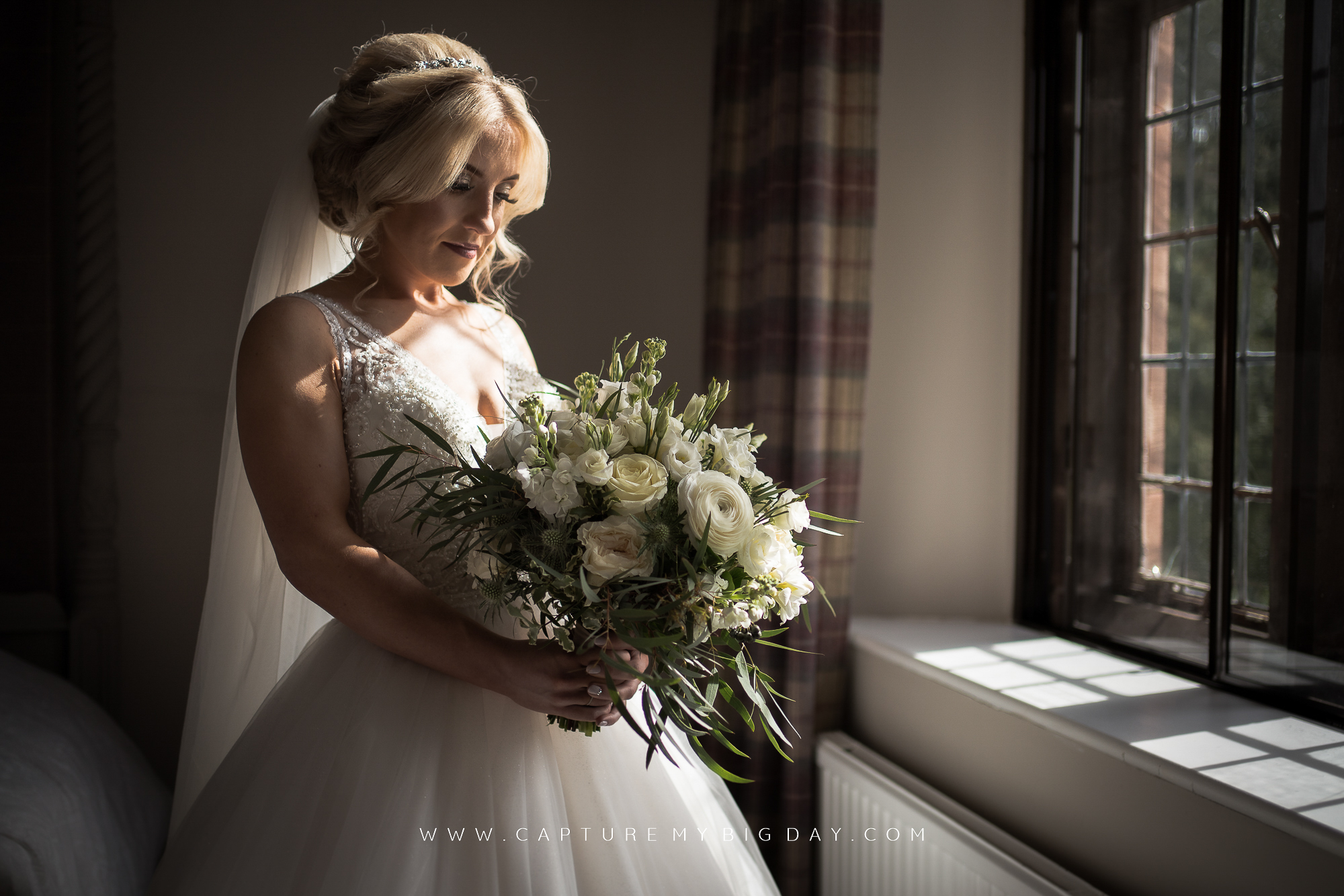 Bride looking at flowers next to window
