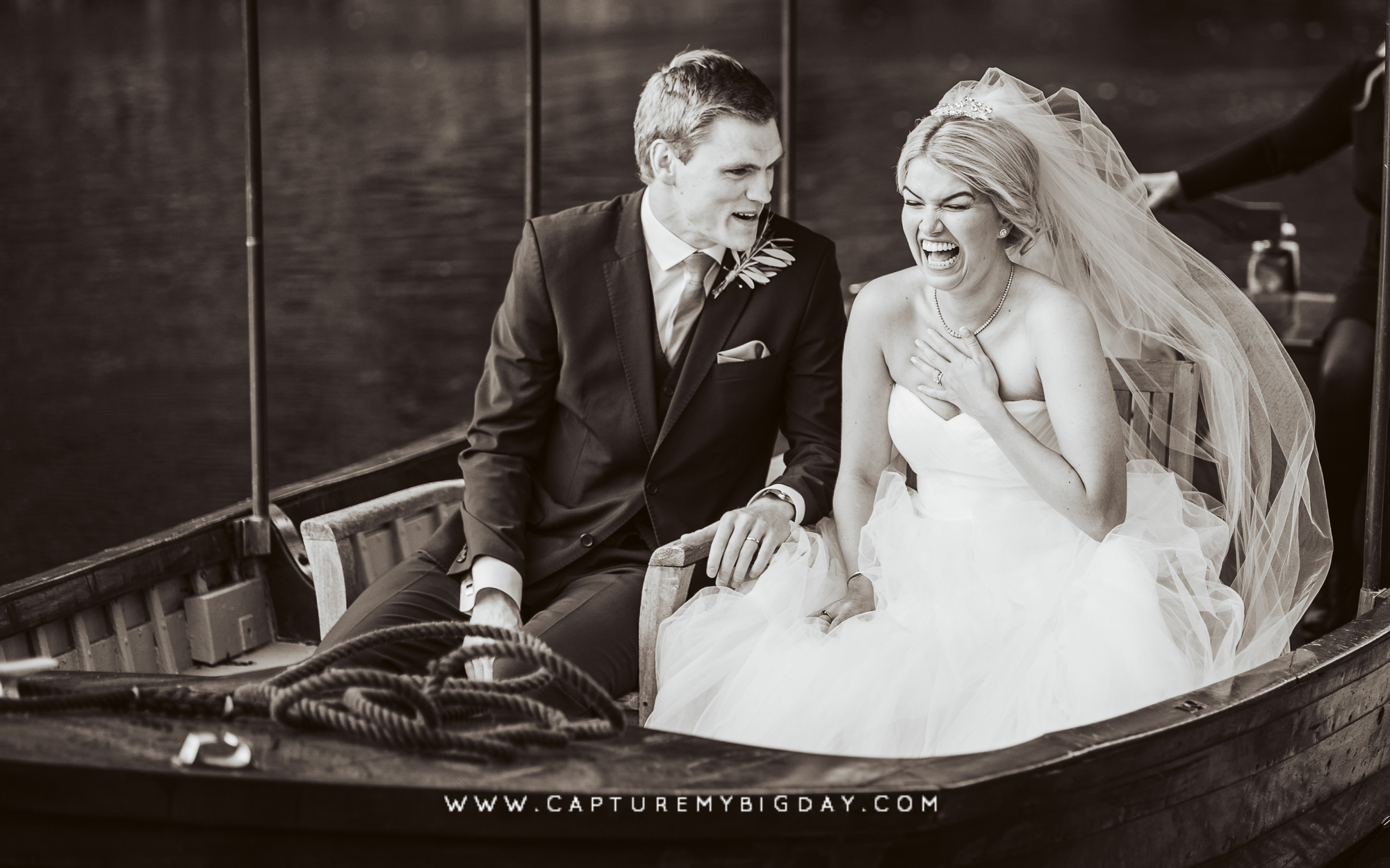 Bride laughing on boat with groom