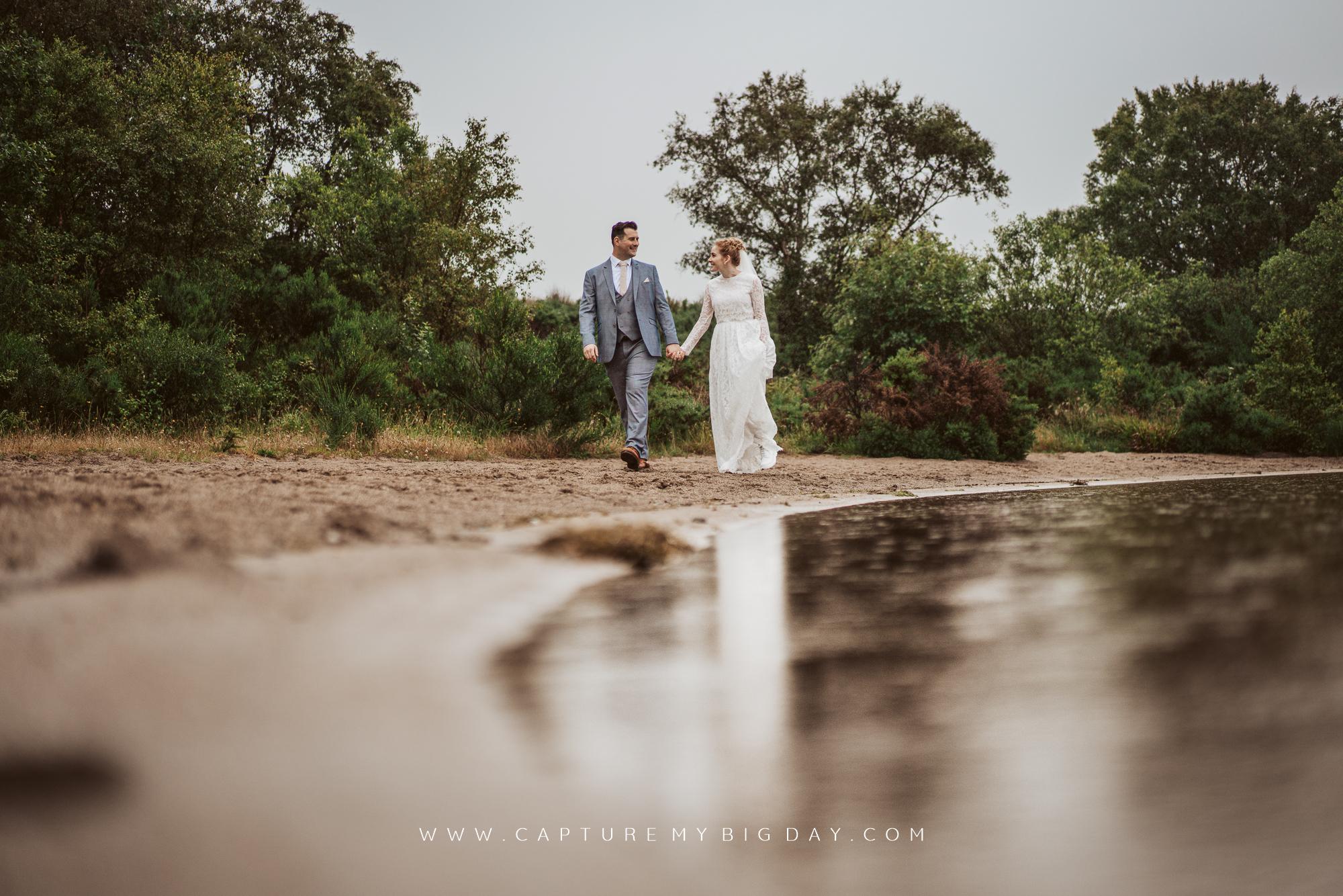 bride and groom walking lakeside