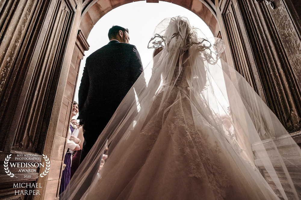 Back of bride and groom as they leave through Wrenbury Hall doors