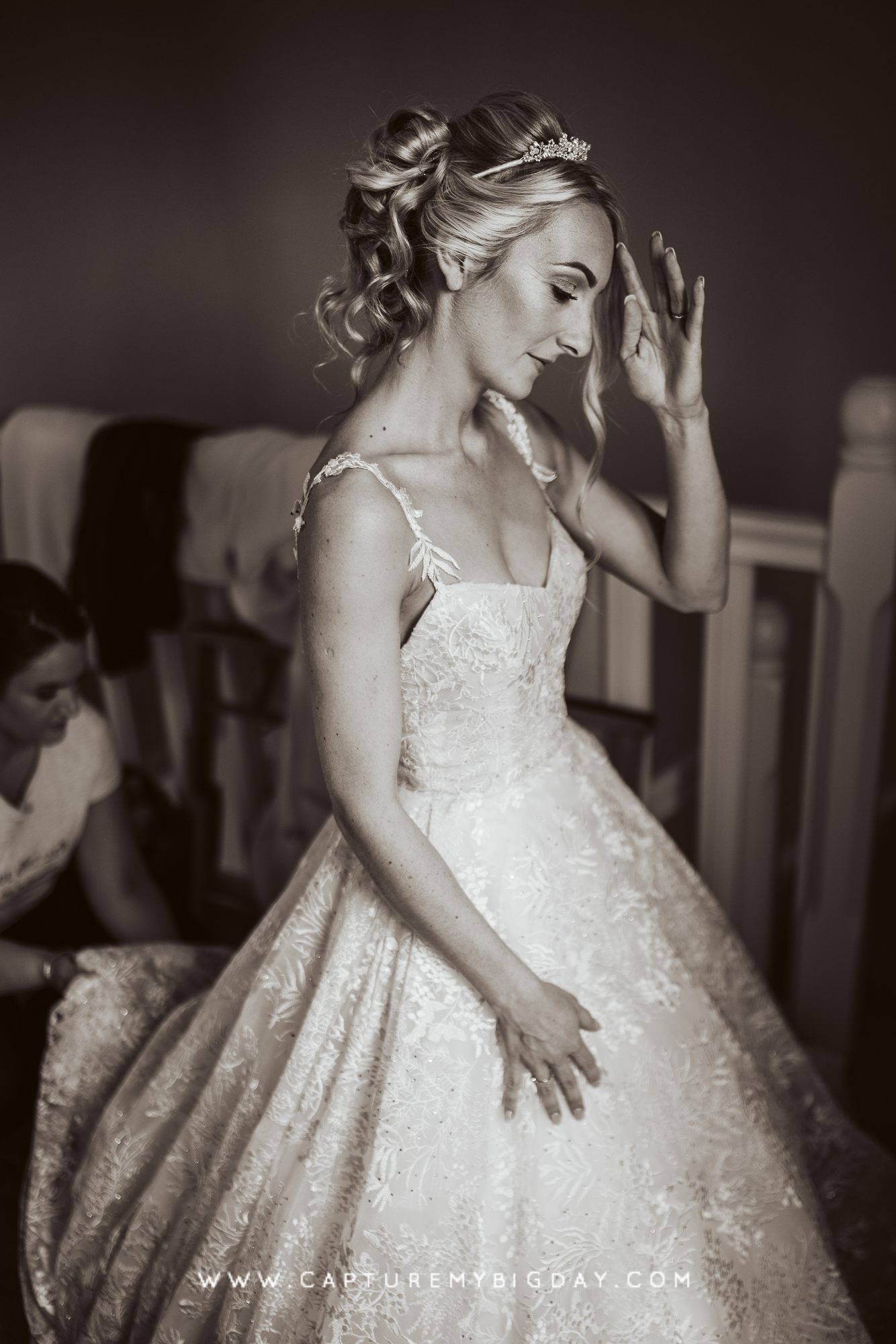 bride in wedding dress with bridesmaid fixing bottom of dress