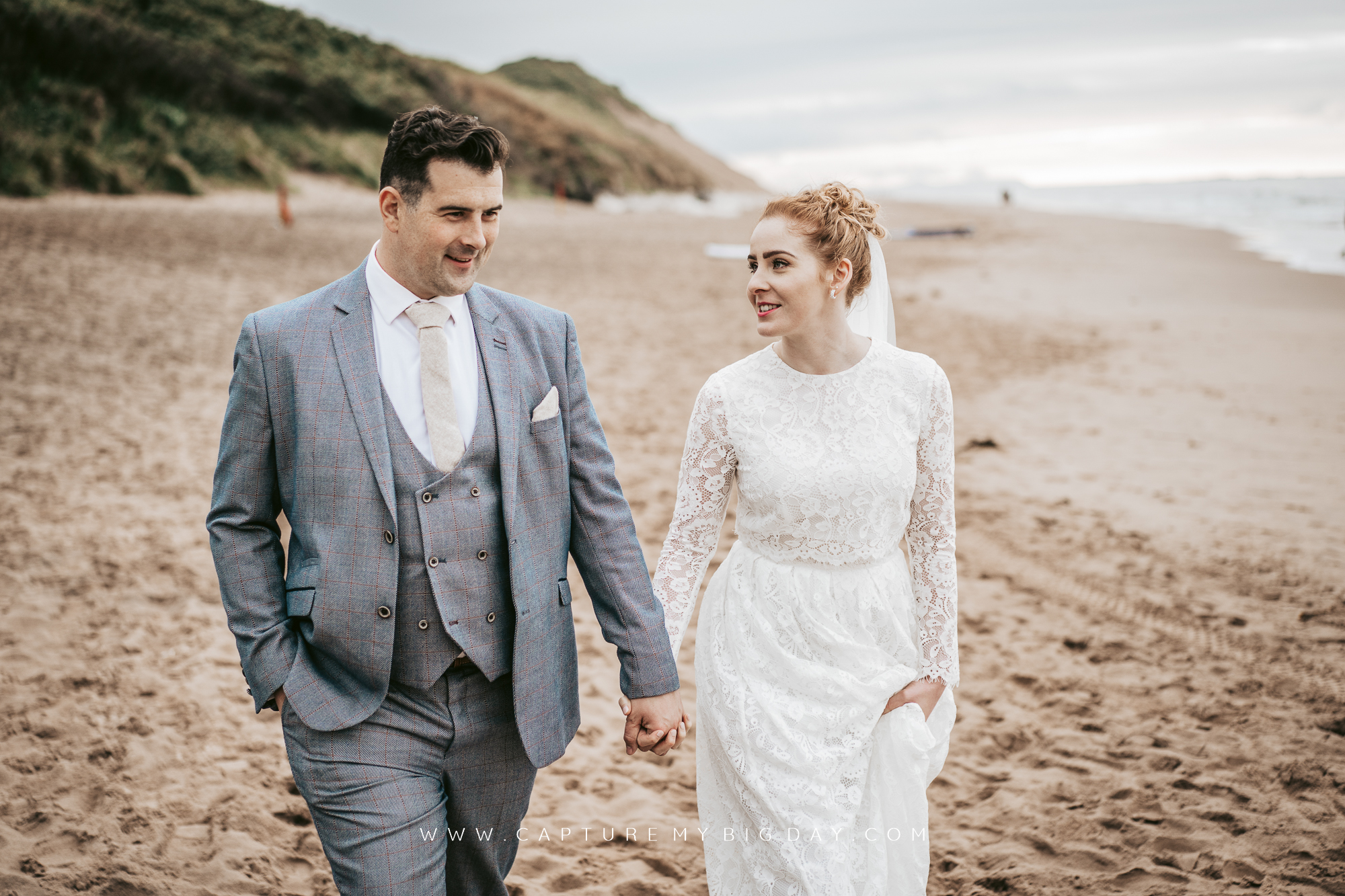 bride and groom walking the beach