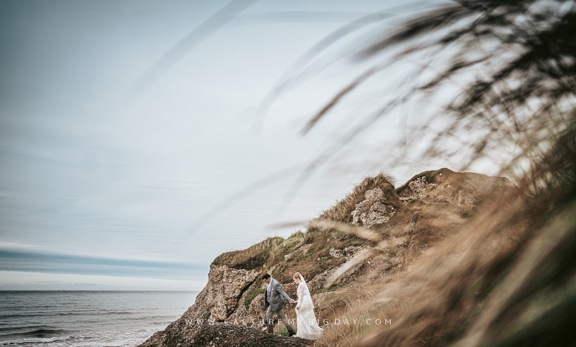 bride and groom walking the cliff edge