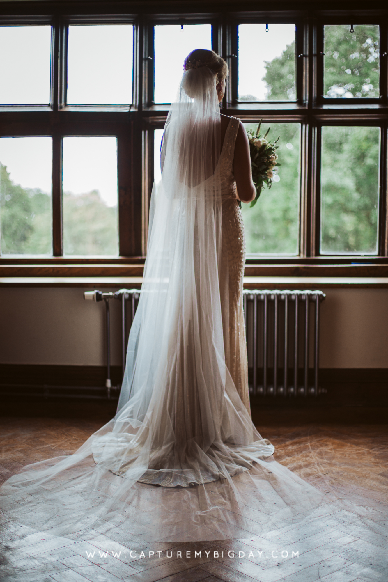 Bride in dress in front of window