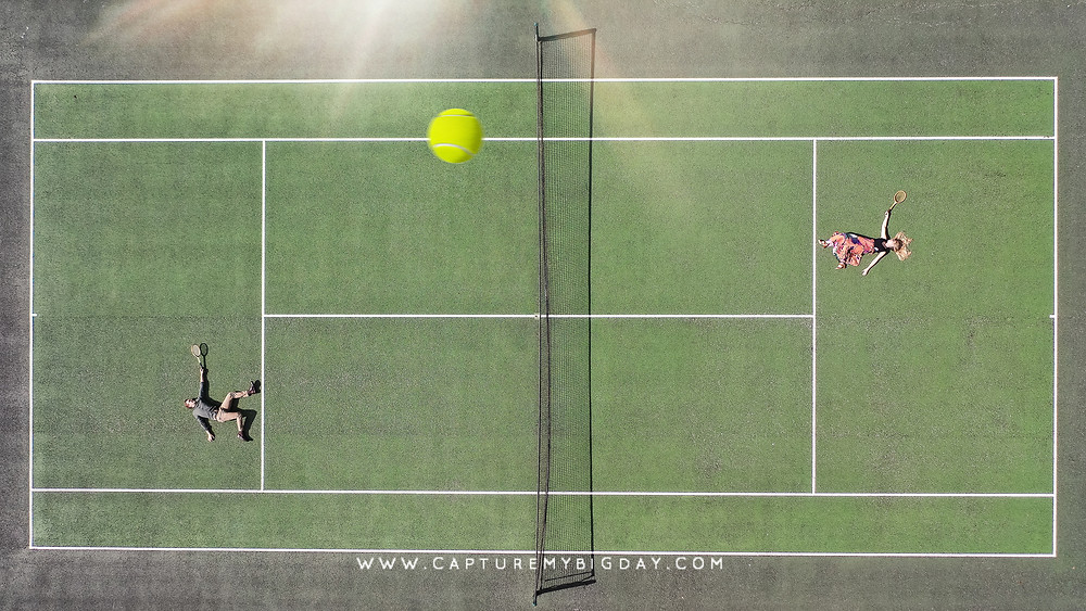 engaged couple playing tennis
