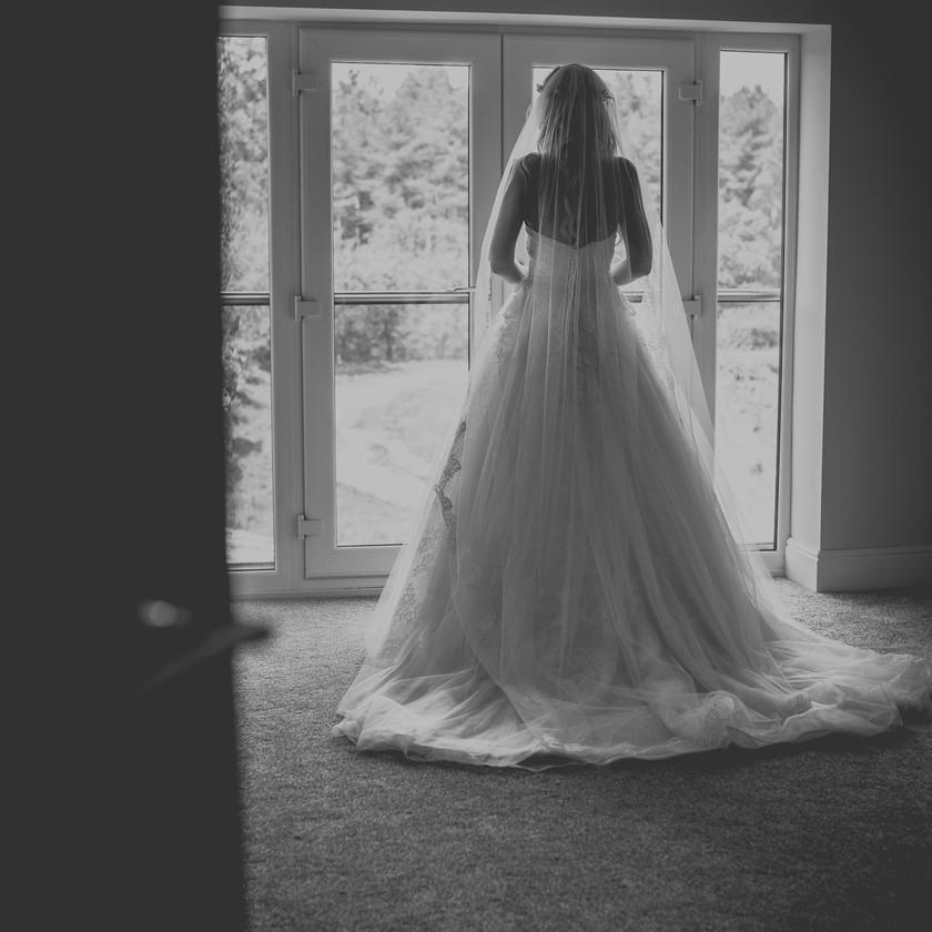 bride in wedding dress looking out of window