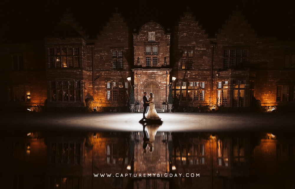 Bride and groom standing outside Wrenbury Hall at night