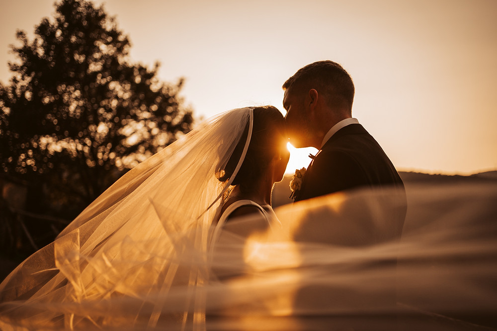 groom kissing bride in Italy as the sun sets