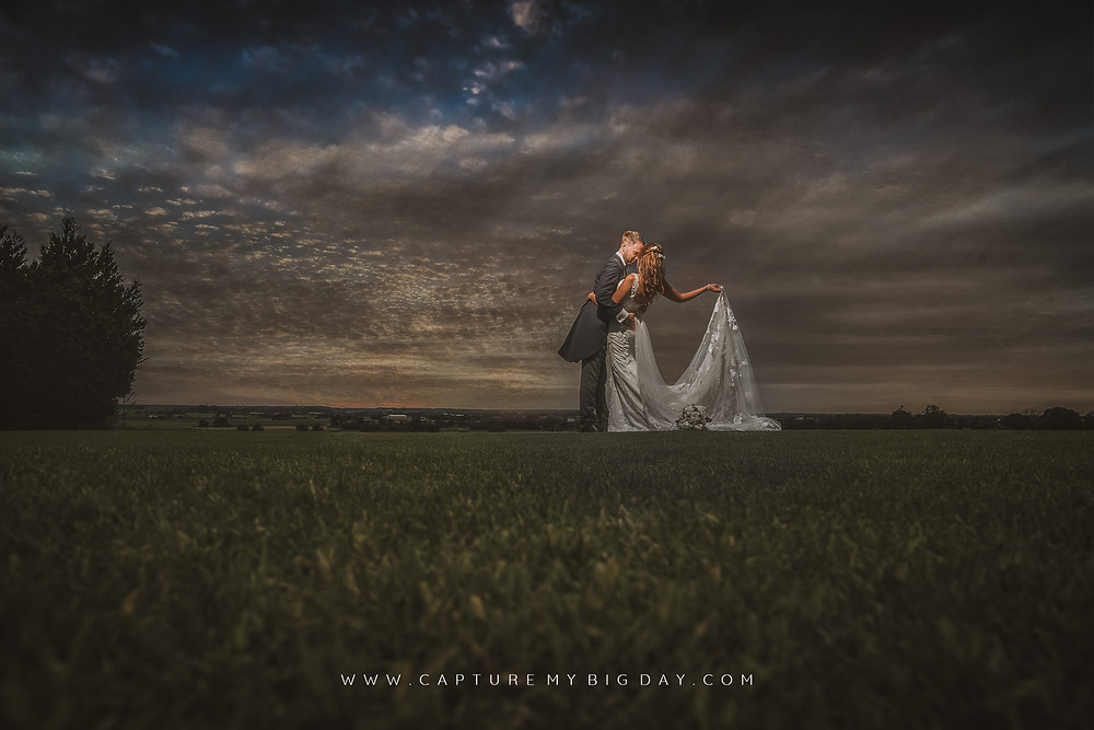 Bride and groom in the evening in a field at West Tower