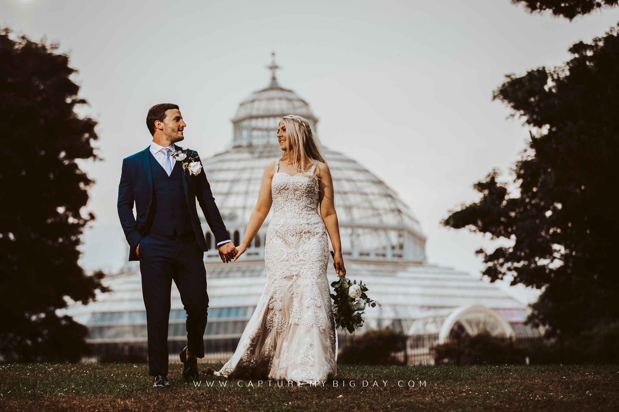 bride and groom walking away from the Palm house