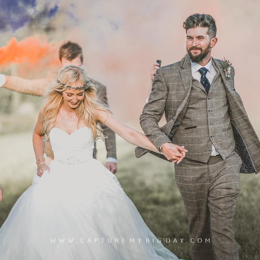 bride and groom walking through smoke