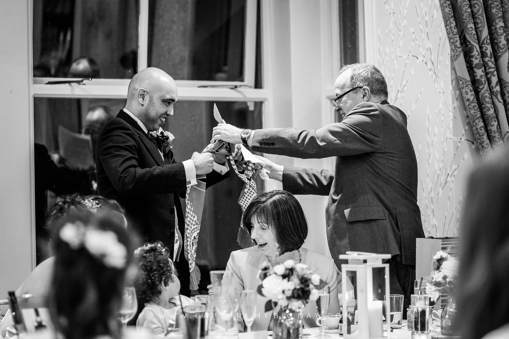 groom opening gift from father of the bride