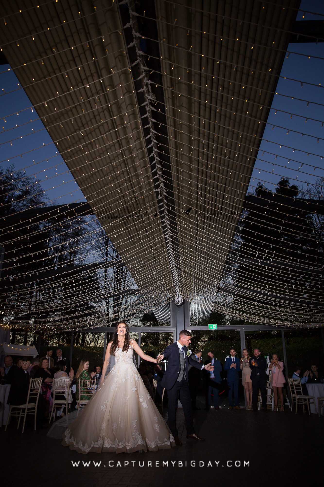 Bride and grooms first dance under fairy lights