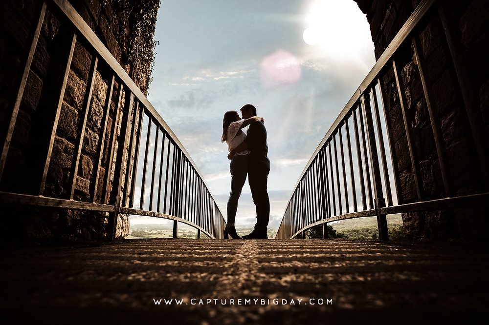 Engaged couple standing on a castle bridge