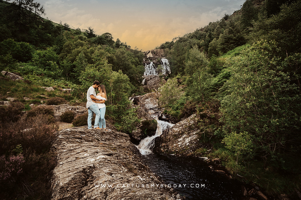 couple standing next to a waterfall