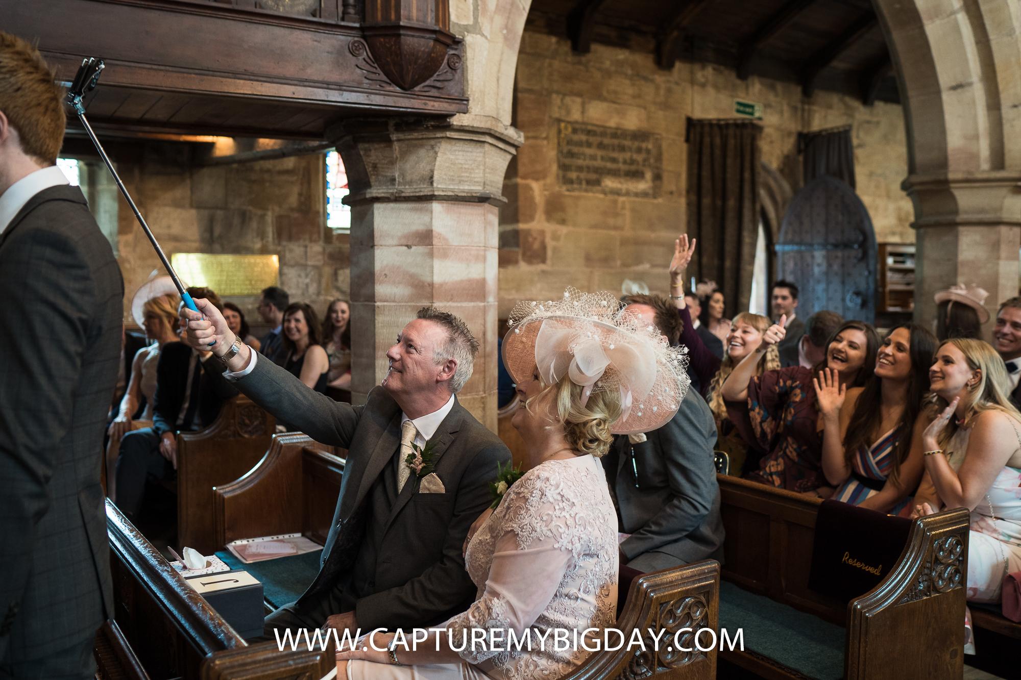 wedding guests taking selfie in church