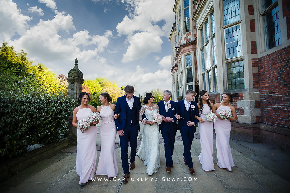 Wedding party walking in a line outside Crewe hall