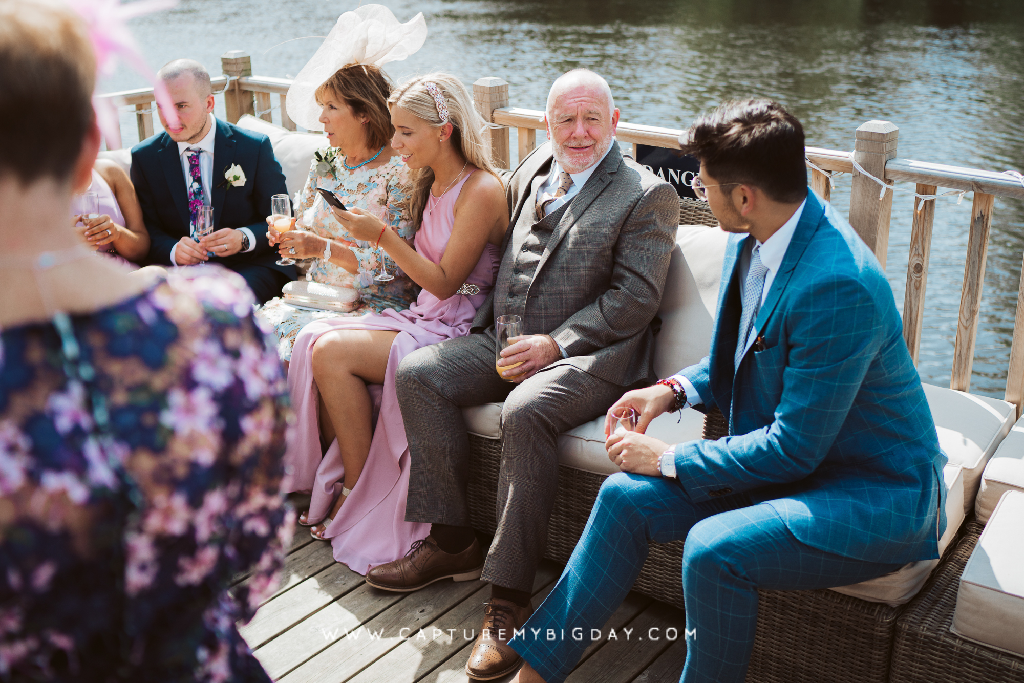 wedding guests drinking by the lake on the decking