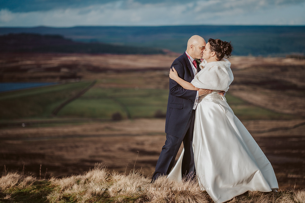 bride & groom  in the wind on the Yorkshire dales