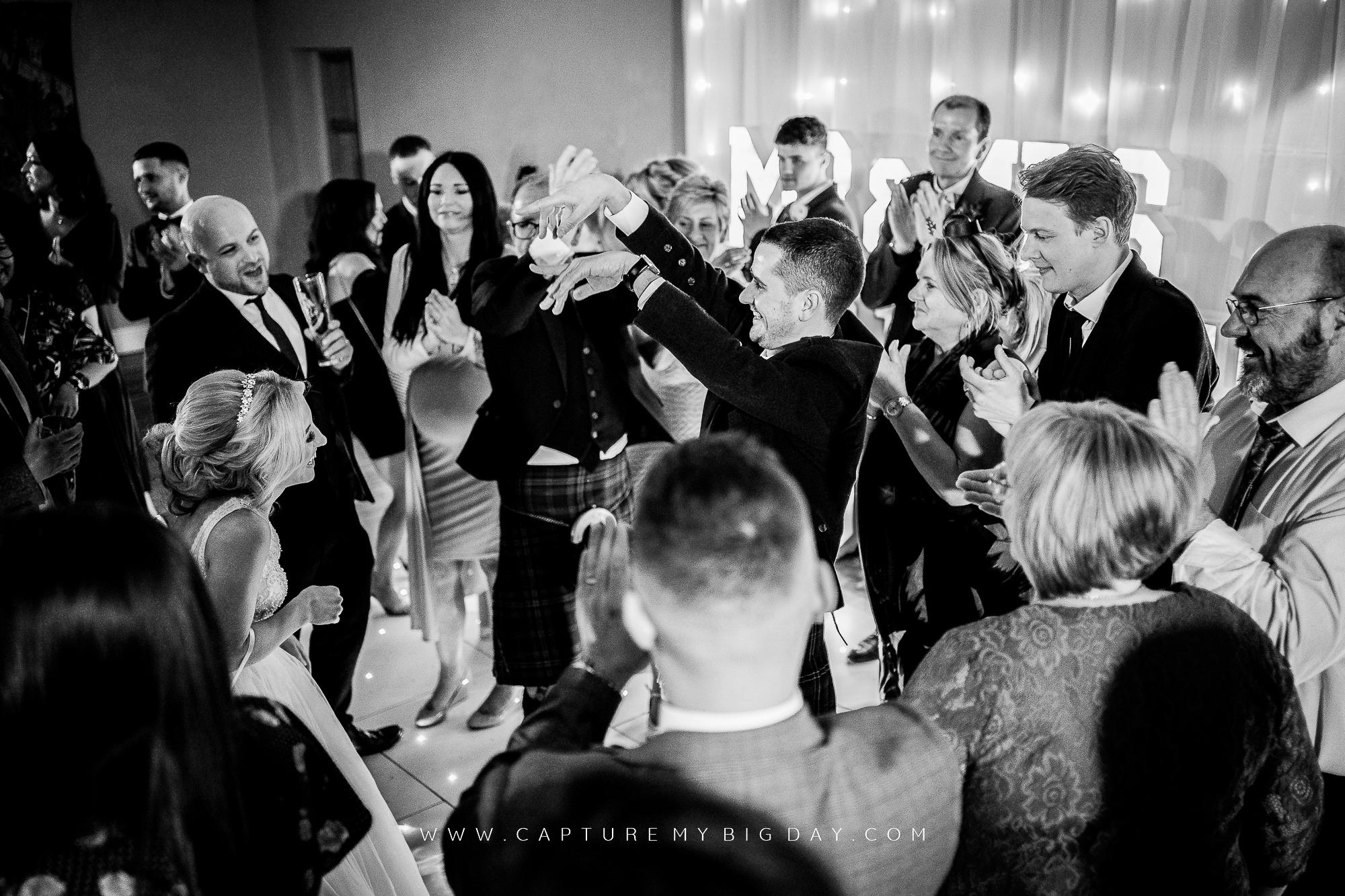 bride and groom with friends on dancefloor