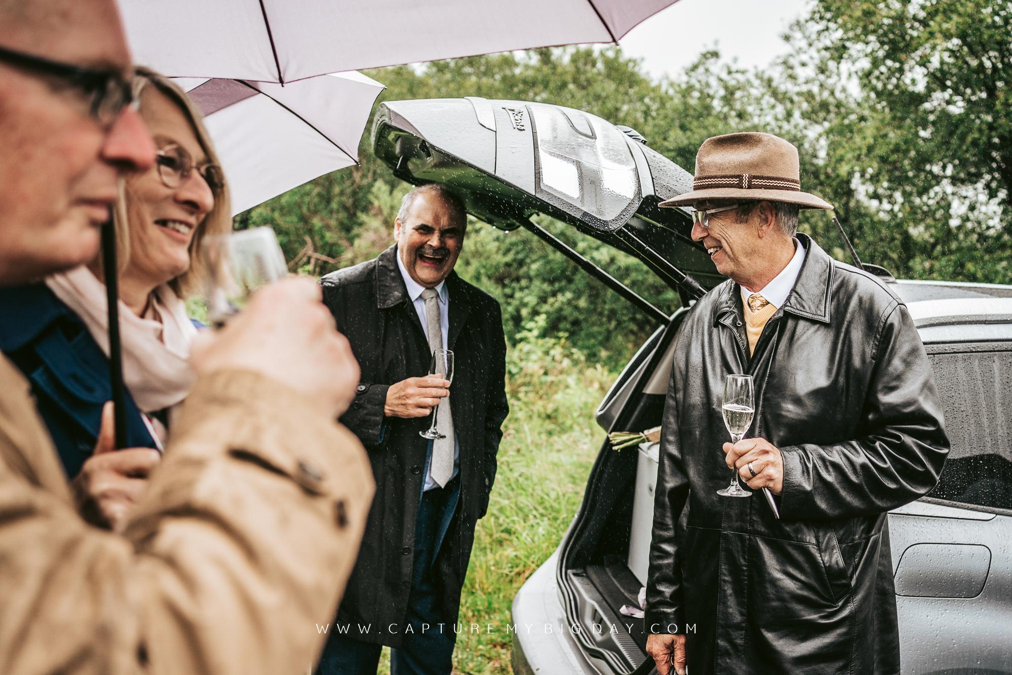 wedding family drinking under umbrella