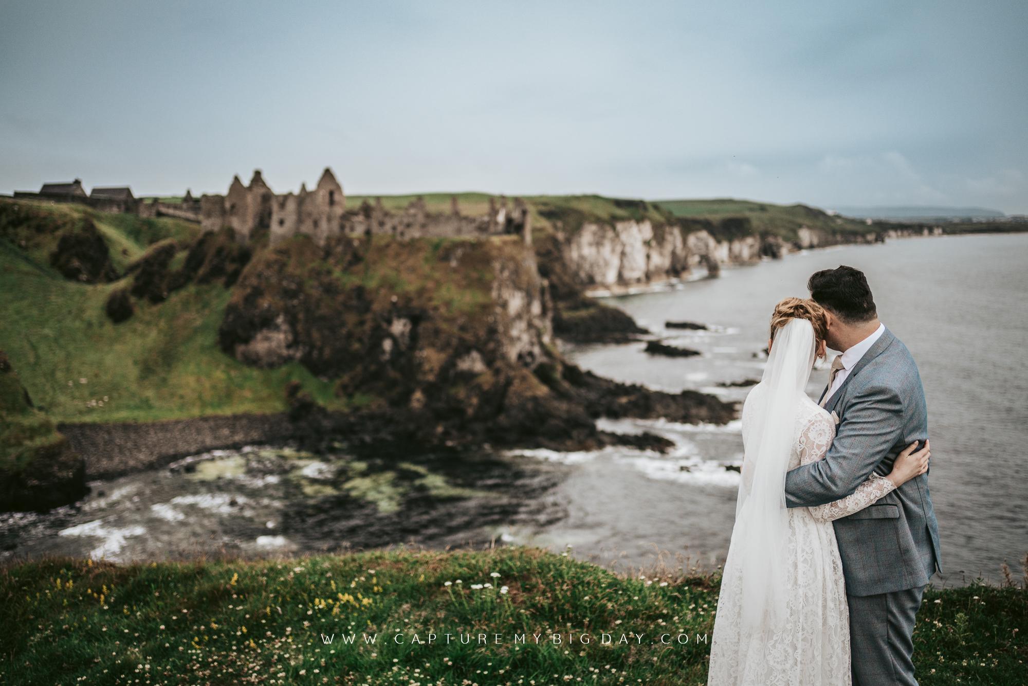 bride and groom with coastline behind them