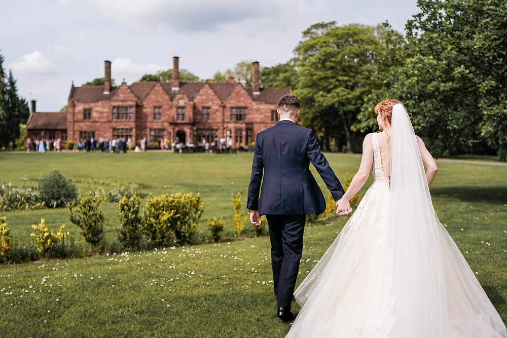 Bride and groom holding hands walking towards Wrenbury Hall