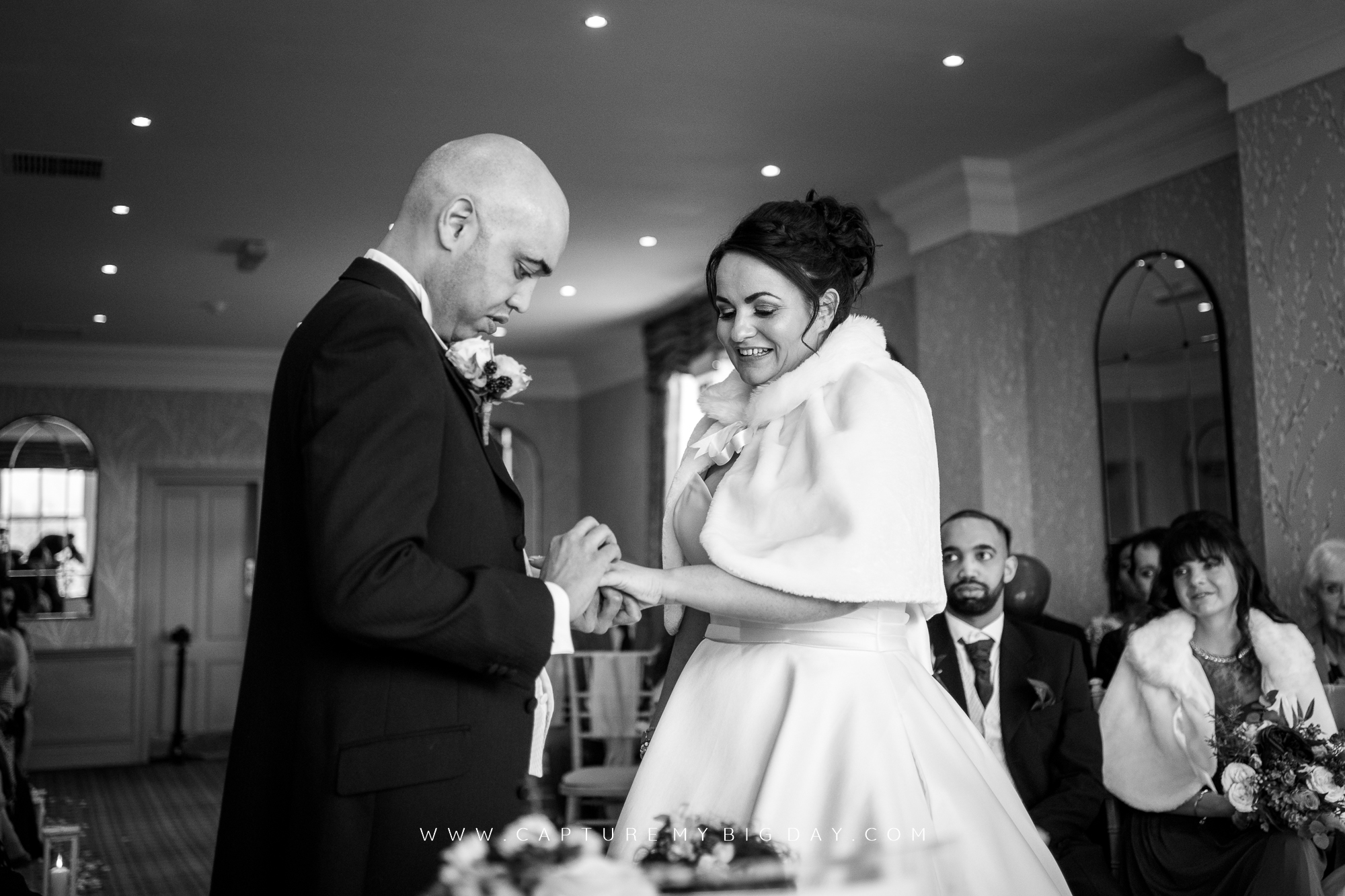 groom saying vows while placing ring on brides finger