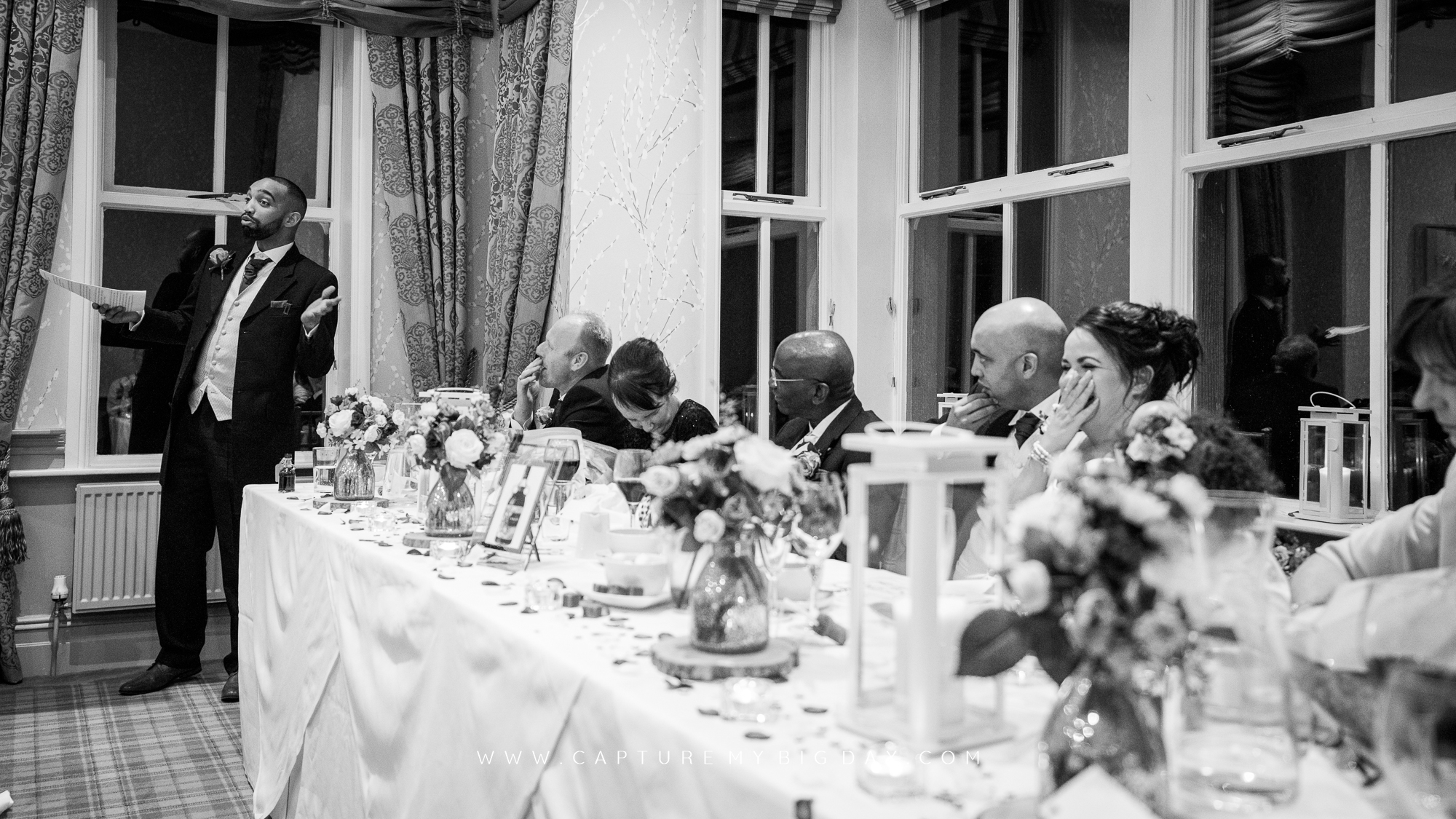 best man reading speech  with bride laughing