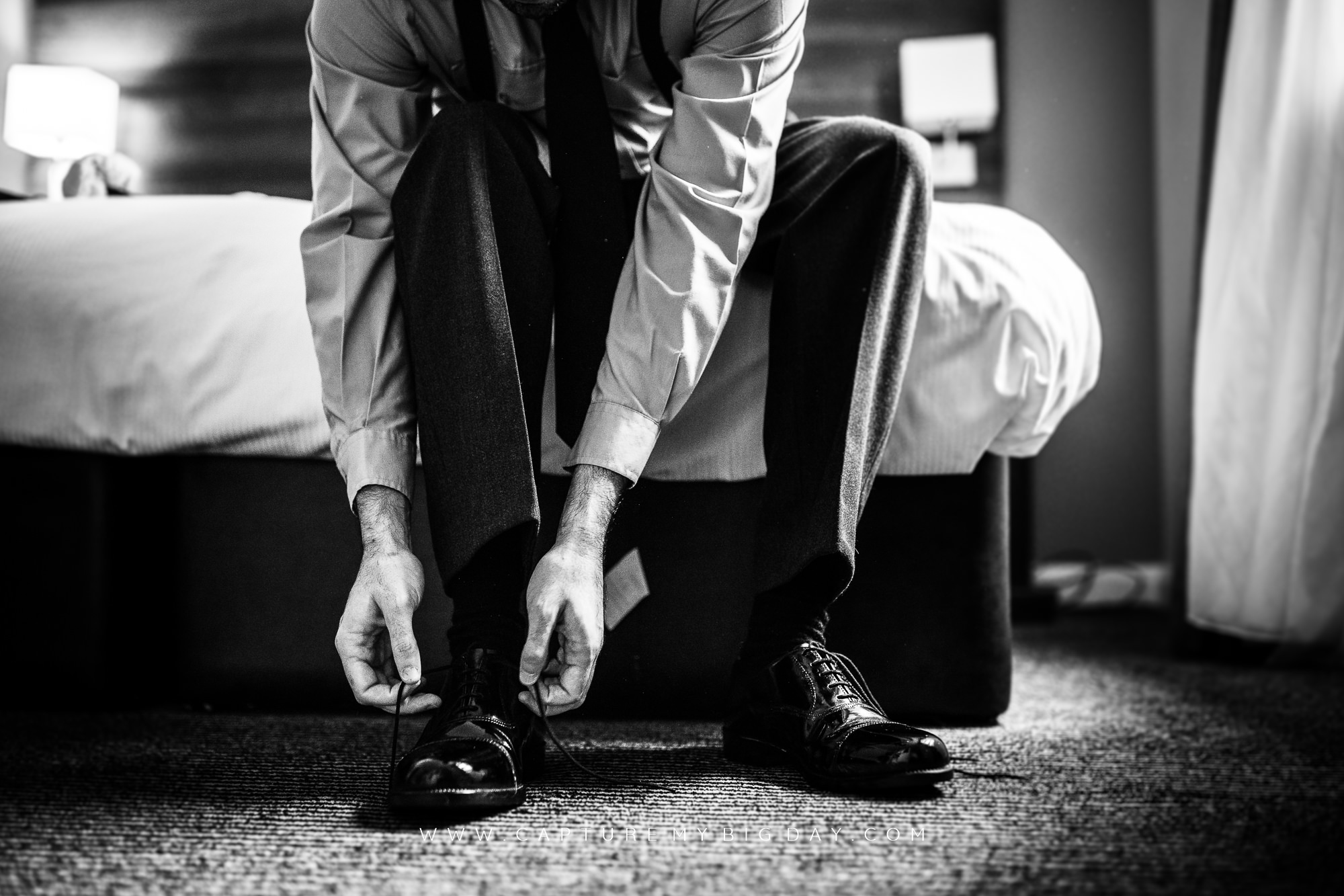 groom putting his shoes on