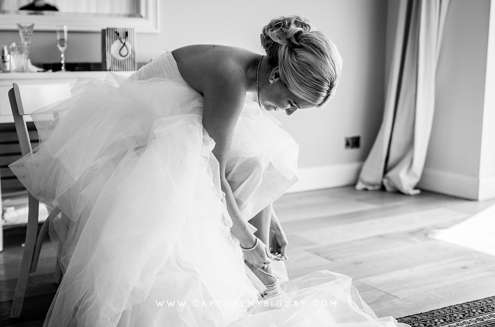 Bride is fastening her shoes with her wedding dress on