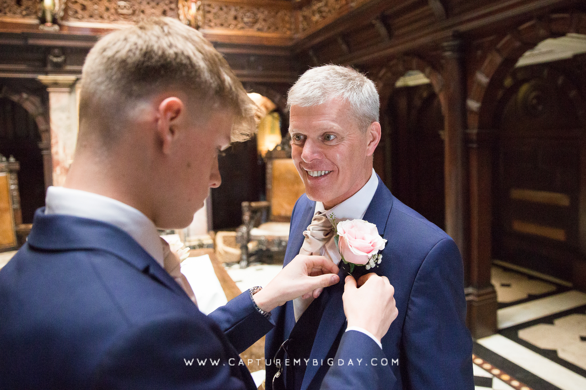 Groom having his buttonhole rose fitted