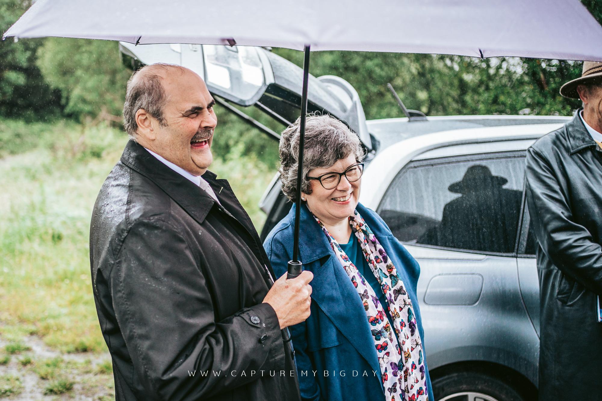 parents laughing under umbrella