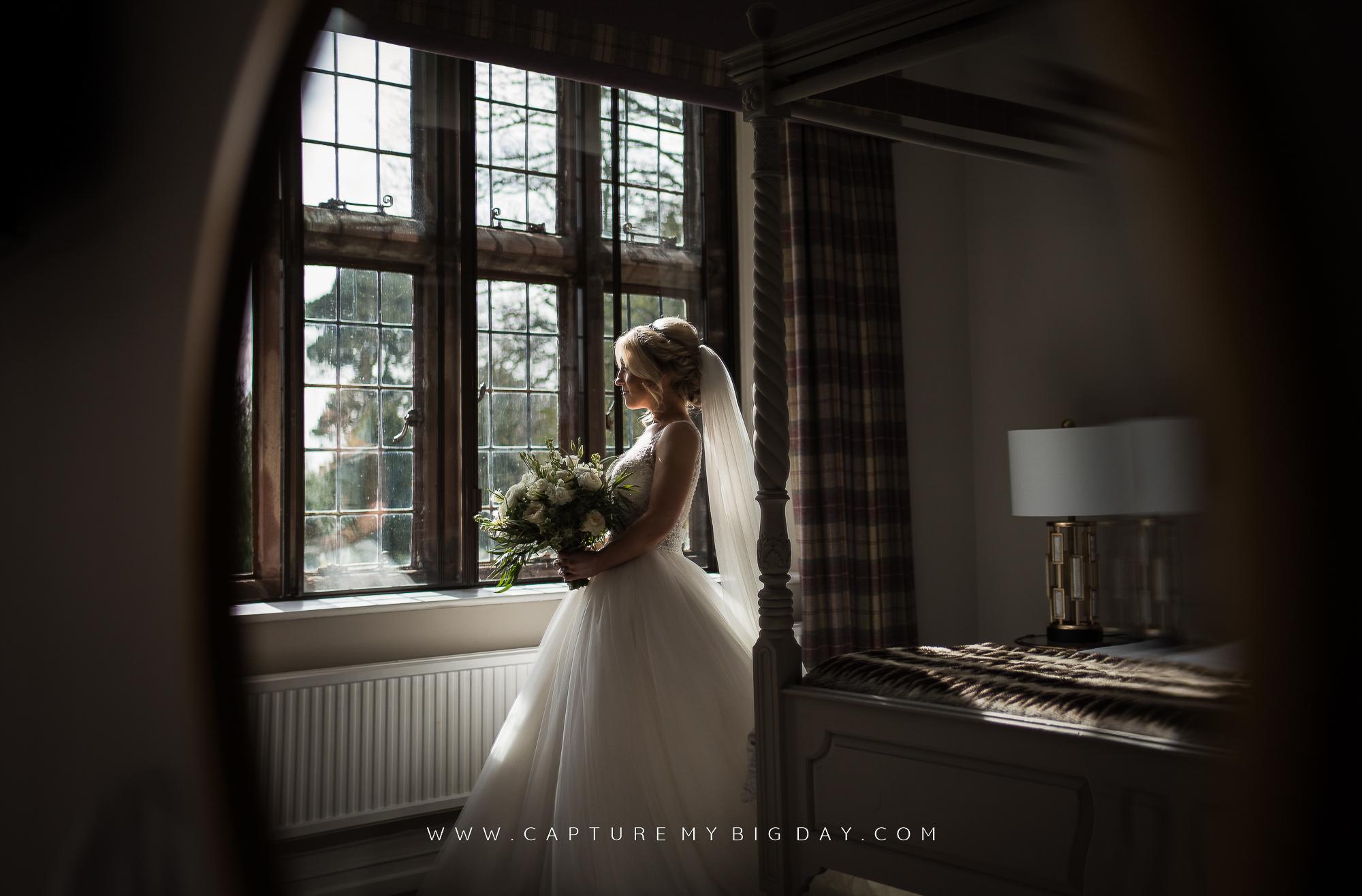 bride looking out of window wearing her wedding dress