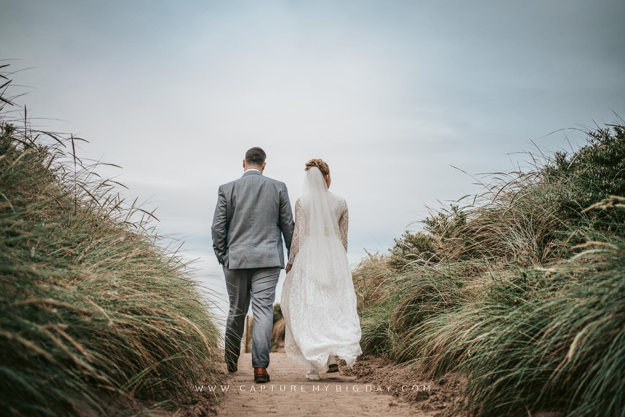 bride and groom walking through long grass towards beach