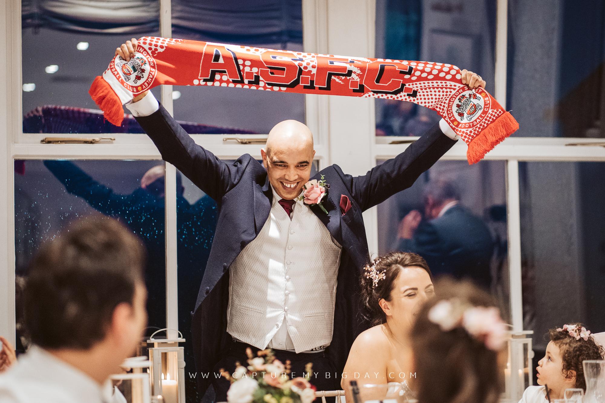 groom holding scarf above head