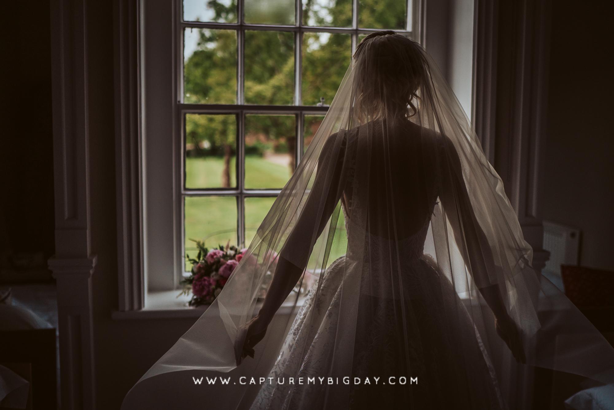 bride looking out of window in wedding dress